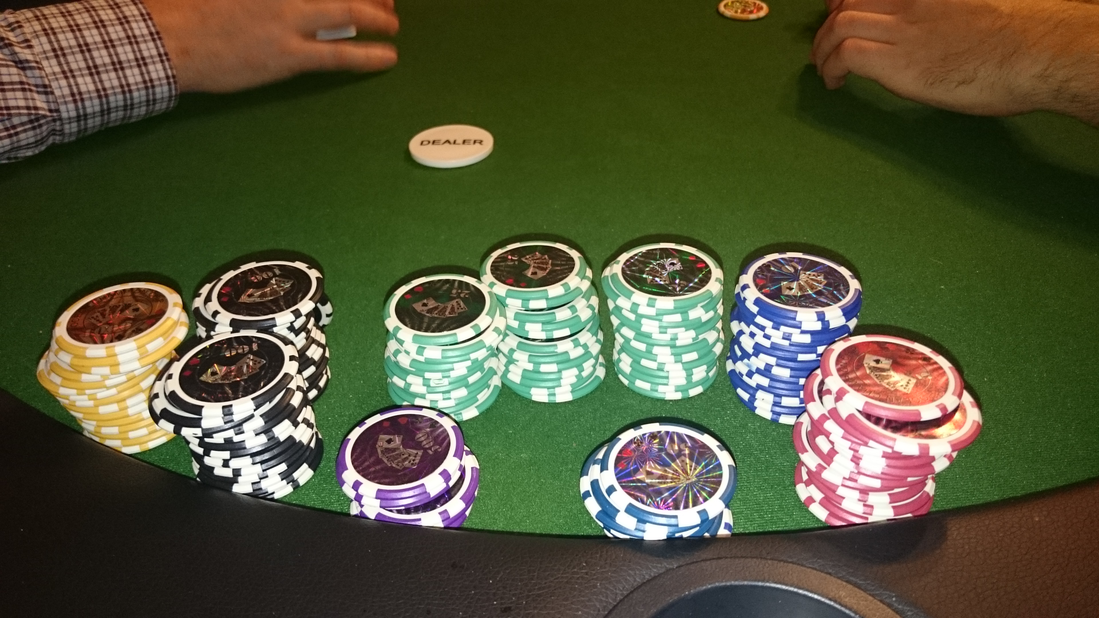 Die Pokerchips am Tisch mit Dealer Button.