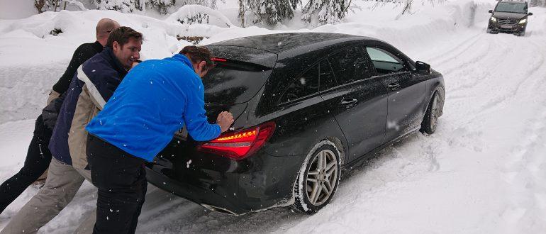 Der Schnee blockiert, Auto wird angeschoben.